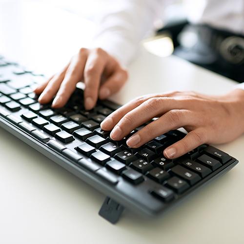 Hände tippen auf Tastatur