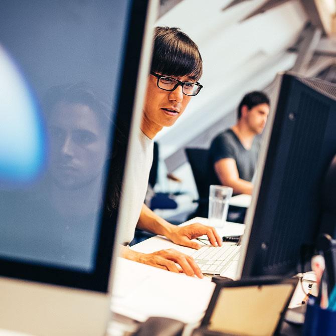 Mann mit Brille arbeitet am Computer